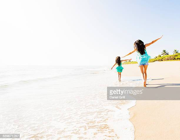 USA, Florida, Jupiter, Rear view of girl (6-7) and her mom running on beach