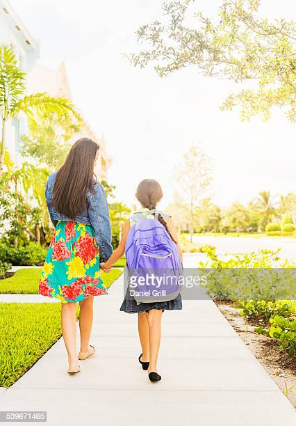 USA, Florida, Jupiter, Rear view of girl (6-7) holding hands with her mom outdoors