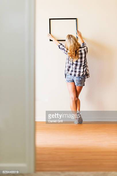 USA, Florida, Jupiter, Rear view of woman hanging picture frame on wall