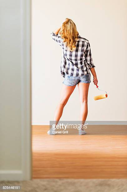 USA, Florida, Jupiter, Rear view of woman holding paint roller
