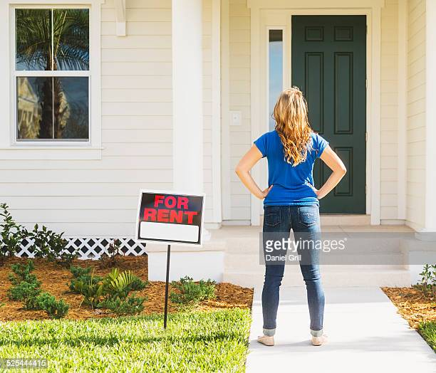 usa, florida, jupiter, rear view of woman standing next to for rent sign - hand on hip stock pictures, royalty-free photos & images