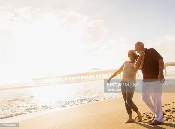 usa, florida, jupiter, senior couple walking on beach - spoor vorm stockfoto's en -beelden
