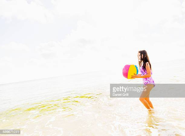 usa, florida, jupiter, side view of girl (6-7) holding beach ball on beach - children only stock photos and pictures