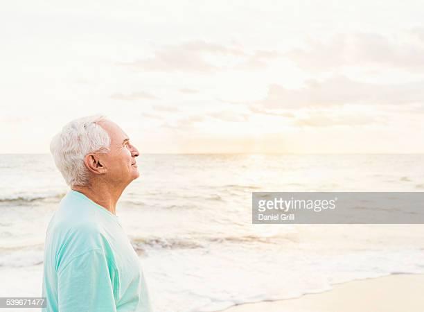 USA, Florida, Jupiter, Side view of senior man smiling on beach