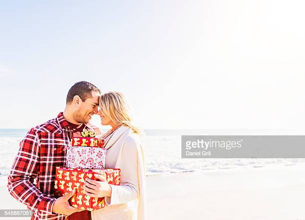 usa, florida, jupiter, smiling couple holding presents on beach - florida christmas stock pictures, royalty-free photos & images