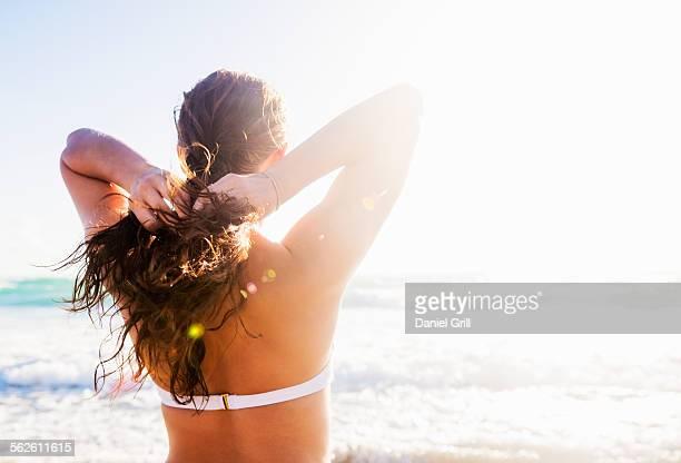 USA, Florida, Jupiter, Woman braiding her hair on beach