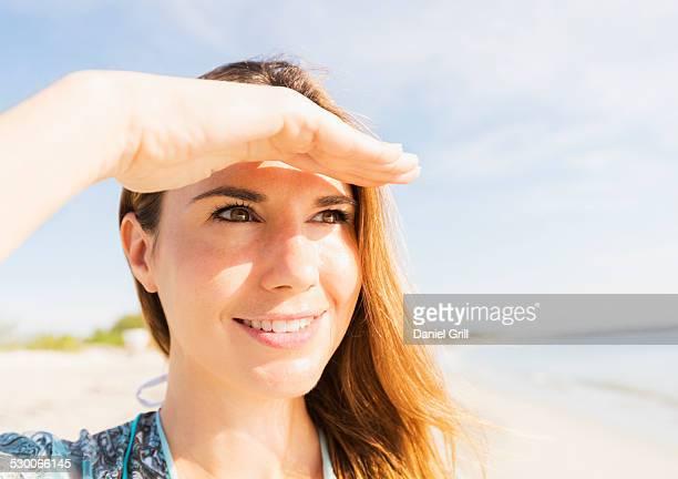 USA, Florida, Jupiter, Woman shielding eyes on beach