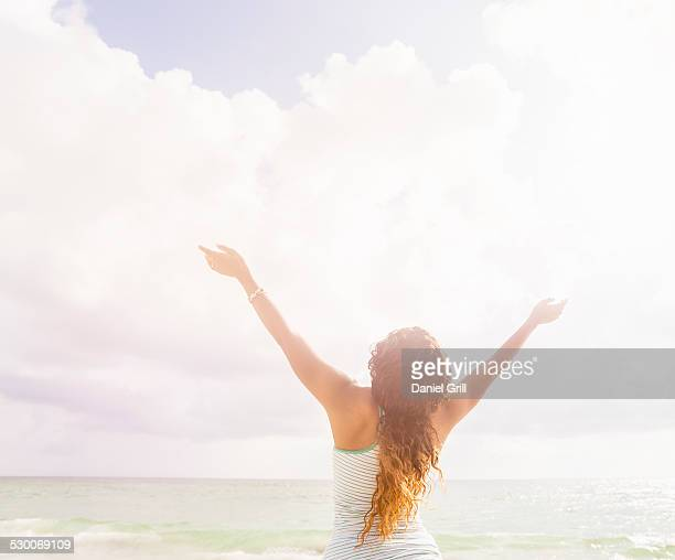 USA, Florida, Jupiter, Woman with arms raised standing on beach