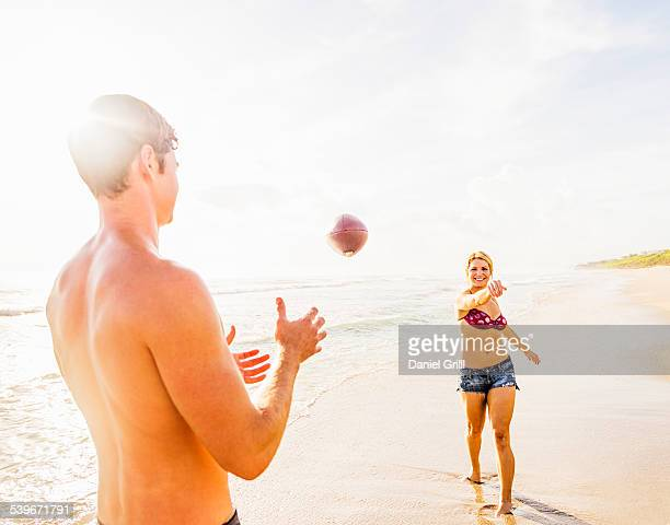 USA, Florida, Jupiter, Young couple throwing football on beach