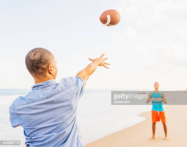 USA, Florida, Jupiter, Young men playing football on beach