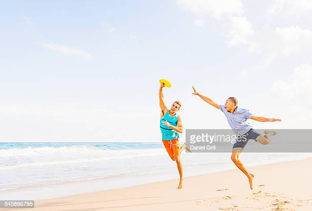 USA, Florida, Jupiter, Young men playing plastic disc on beach