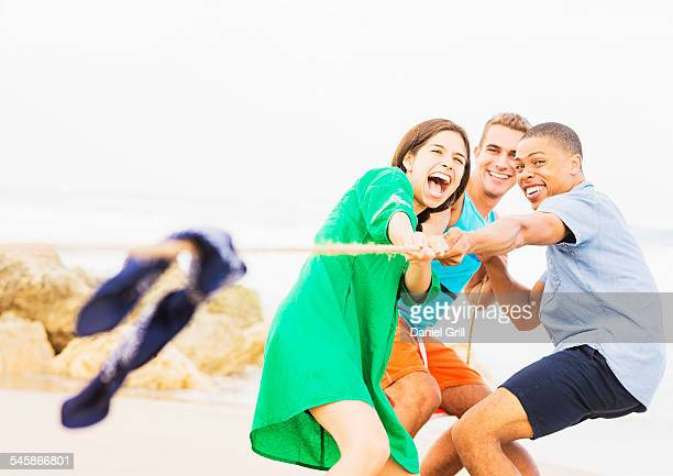 USA, Florida, Jupiter, Young people pulling rope on beach