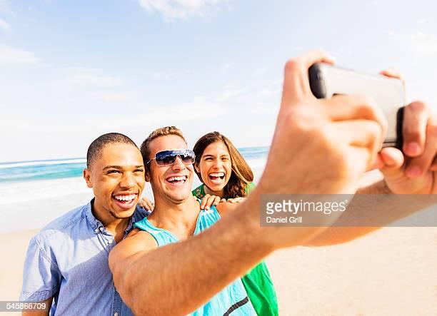 USA, Florida, Jupiter, Young people taking selfie on beach