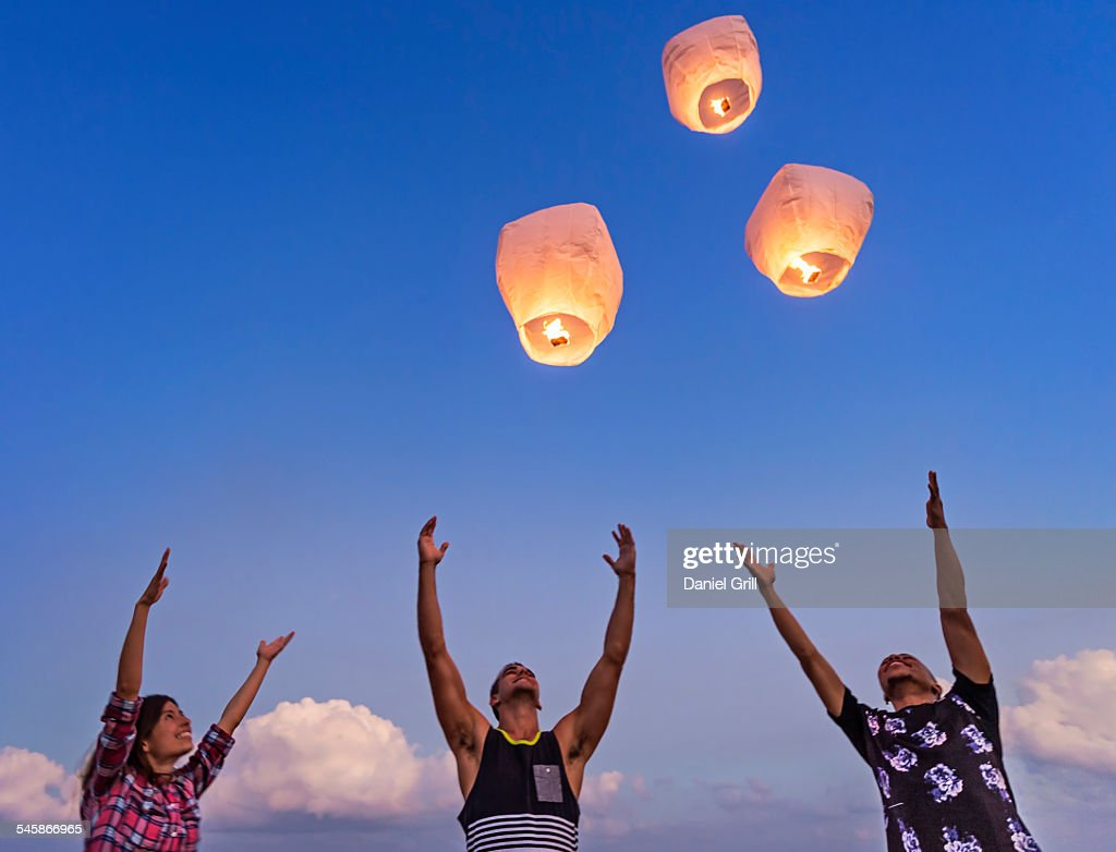 USA, Florida, Jupiter, Young people with illuminated lanterns at sunset : Stock Photo