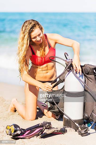 USA, Florida, Jupiter, Young woman kneeling on sandy beach putting together scuba diving equipment