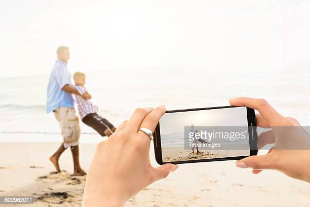 usa, florida, jupiter, young woman photographing father with son (12-13) on beach - photo messaging stock photos and pictures