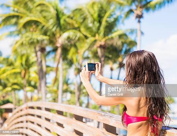 USA, Florida, Jupiter, Young woman photographing wooden bridge