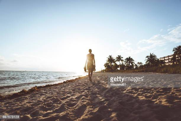 usa, florida, key west, woman walking on the beach at sunset - key west stock photos and pictures