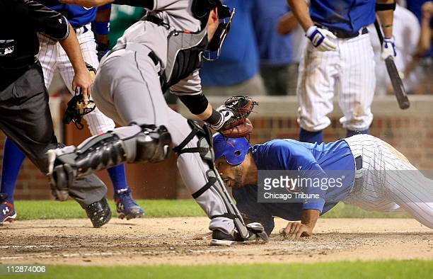 Florida Marlins catcher John Baker tags out Chicago Cubs' Derrek Lee as he tries to score on a bases loaded hit by teammate Aramis Ramirez in the...