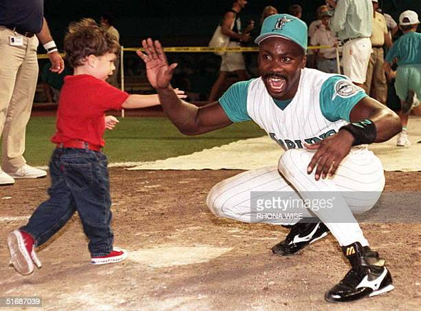 Florida Marlin's centerfielder Chuck Carr holds out his hand to Tyler Jove as he crosses home plate at Joe Robbie stadium in Miami FL 30 July Every...