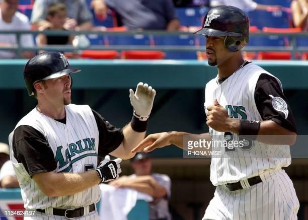 Florida Marlins' first baseman Derek Lee is congratulated at home plate by Marlins' catcher Mike Redmond after Lee scored the winning run on a Dave...
