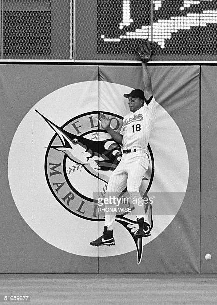 Florida Marlins outfielder Moises Alou misplays a ball hit deep into the outfield by Colorado Rockies first baseman Andres Galarraga which fells for...