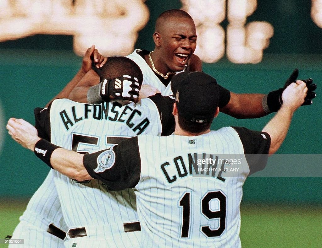 Florida Marlins player Edgar Renteria (C) celebrates his game-winning hit against the Cleveland Indians with teammates Antionio Alfoseca (L) and Jeff Conine 26 October after game seven of the World Series at Pro Player Stadium in Miami, FL. The Marlins beat the Indians 3-2 in 11 innings to win the World Series. AFP PHOTO/Timothy A. CLARY