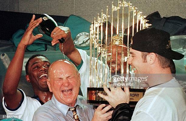 Florida Marlins player Edgar Renteria Gary Sheffield and Tony Saunders celebrate their 32 win in game seven of the World Series with owner Wayne...