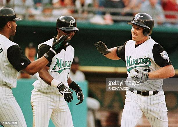 Florida Marlins second baseman Kurt Abbott is greeted outside the dugout by teammates Gary Sheffield and Edgar Renteria after he crosses the plate...