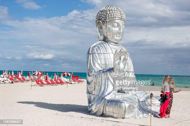 Florida, Miami Beach, Art Basel Week, Buddha beach sculpture, Chinese artist Zhang Huan, with women posing.