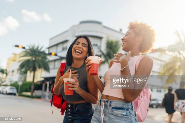 usa, florida, miami beach, two happy female friends having a soft drink in the city - city_(florida) stock pictures, royalty-free photos & images