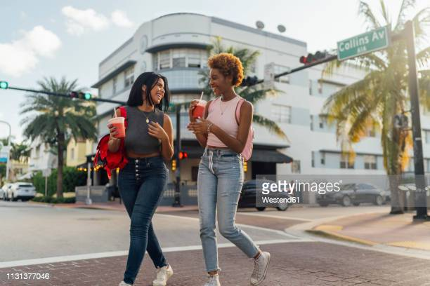 usa, florida, miami beach, two happy female friends having a soft drink crossing the street - south beach stock pictures, royalty-free photos & images