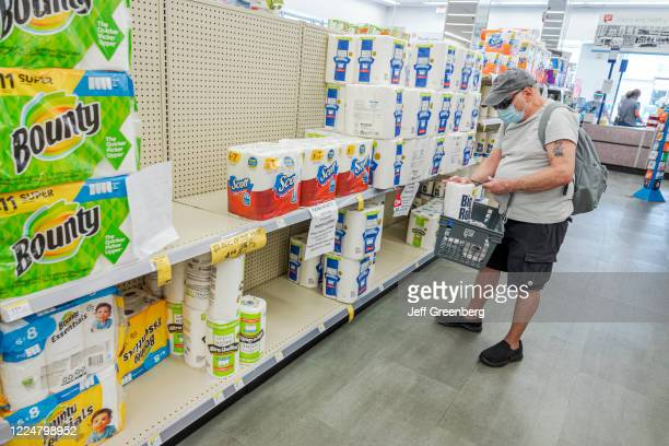 Florida, Miami Beach, Walgreens pharmcy, Man in face mask buying paper towels during Coronavirus Pandemic.