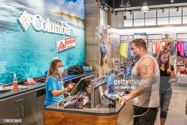 Florida, Orlando, Walt Disney World Resort, Columbia Sportswear, store worker with customers one wearing face mask improperly.