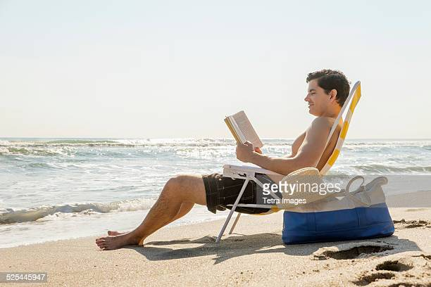 USA, Florida, Palm Beach, Side view of man sitting on deckchair and reading book