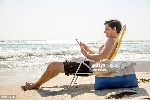 USA, Florida, Palm Beach, Side view of man sitting on deckchair and using digital tablet