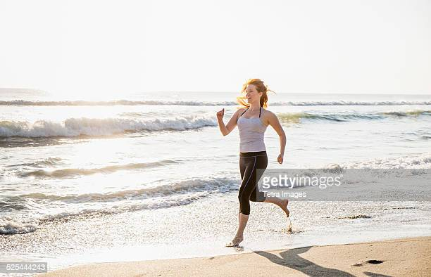 USA, Florida, Palm Beach, Woman running on beach