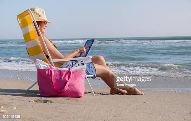 USA, Florida, Palm Beach, Woman sitting on deckchair and using laptop