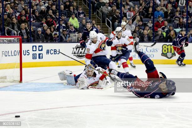 Florida Panthers goaltender James Reimer trips Columbus Blue Jackets right wing Josh Anderson as he blocks a shot in the first period of a game...