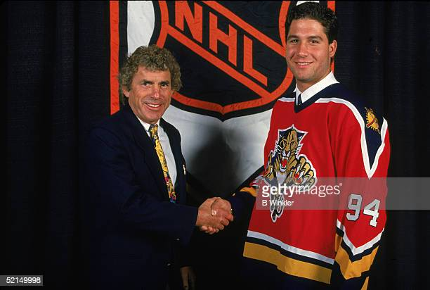 Florida Panthers head coach Roger Neilson shakes hands with Canadian hockey player Ed Jovanovski in front of an NHL logo shortly after the Panthers...