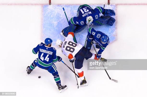 Florida Panthers Left Wing Jamie McGinn is checked to the ice by Defenceman Alexander Edler and Vancouver Canucks Defenceman Erik Gudbranson during...