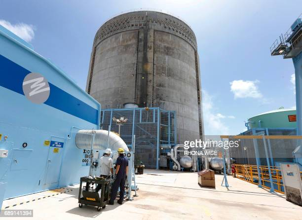 Florida Power and Light workers Juan Madruga and Pehter Rodriguez confer at the Turkey Point Nuclear Reactor Building in Homestead Florida May 18...