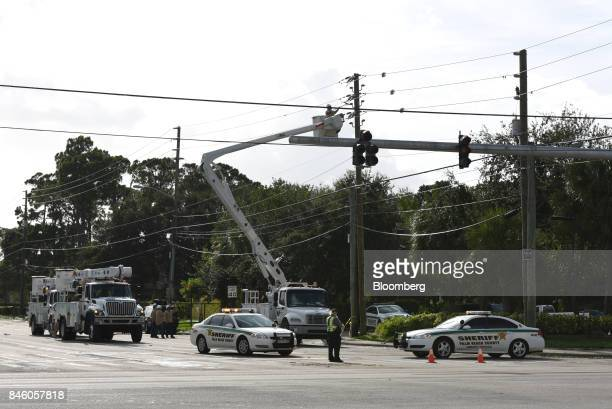 Florida Power Light Co crews work on downed power lines from Hurricane Irma as Palm Beach County Sheriff officers block an intersection in West Palm...
