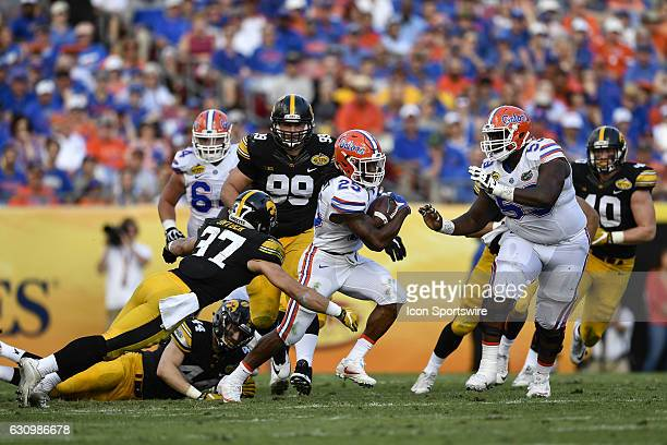 Florida running back Jordan Scarlett tries to run away from the tackle of Iowa defensive back Brandon Snyder during the first half of the Outback...