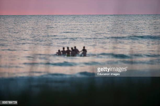 Florida, Siesta Key, Crescent Beach, Pink Sky, Fishermen retrieving a net.