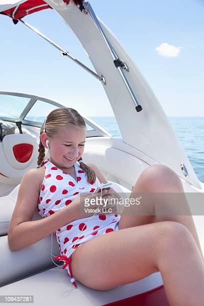 usa, florida, st. petersburg, girl (10-11) listening to mp3 player on boat at sea - one piece swimsuit stock pictures, royalty-free photos & images