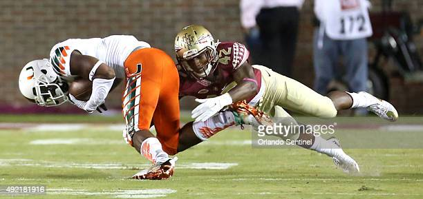 Florida State defensive back Lamarcus Brutus right tackles Miami wide receiver Stacy Coley at Doak Campbell Stadium in Tallahassee Fla on Saturday...