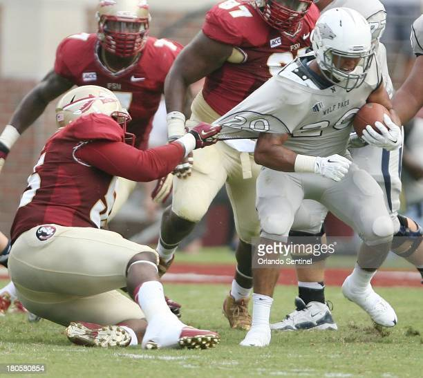 Florida State defensive tackle Jacobbi McDaniel left pulls on the jersey of Nevada running back Chris Solomon during game action at Doak Campbell...
