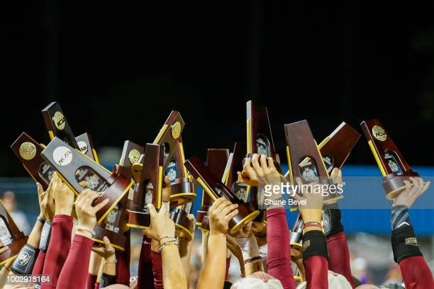 Florida State players hoist their individual national championship trophies following game two of the Division I Women's Softball Championship held...