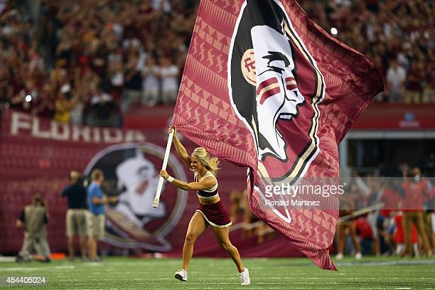 Florida State Seminoles cheerleader runs a flag on the field before a game against the Oklahoma State Cowboys at ATT Stadium on August 30 2014 in...